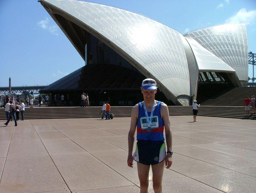 Like etter målpassering ved Sydney Opera House med medalje rundt halsen.